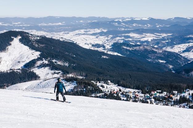 Человек сноубордист на вершине склона. красивые зимние горы. зимние каникулы. копировать пространство. экстремальный спорт