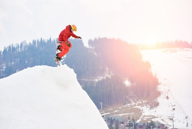 Man snowboarder jumping from the top of the snowy hill with snowboard in the evening at sunset