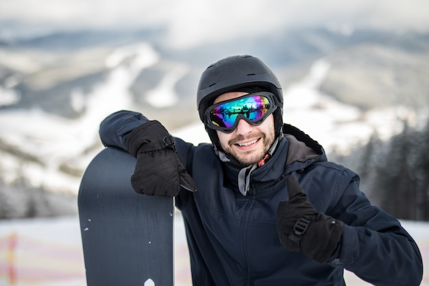 Snowboarder uomo in piedi sulla cima del pendio innevato con lo snowboard, sorridendo alla telecamera, mostrando i pollici in su alla stazione sciistica invernale.