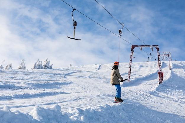 山のウィンタースポーツの頂上に乗るためにスキーヨークを使用して男のスノーボーダー