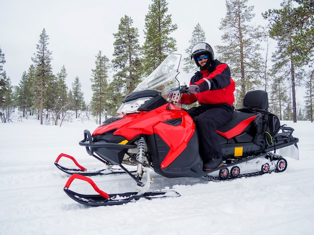 A man on snowmobile in winter mountain