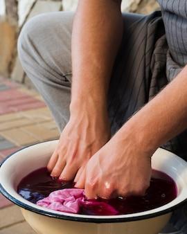 ピンクの天然色素に布を浸す男