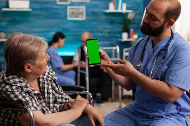 격리된 디스플레이가 있는 모의 녹색 화면 크로마 키를 보고 있는 남자 사회 복지사