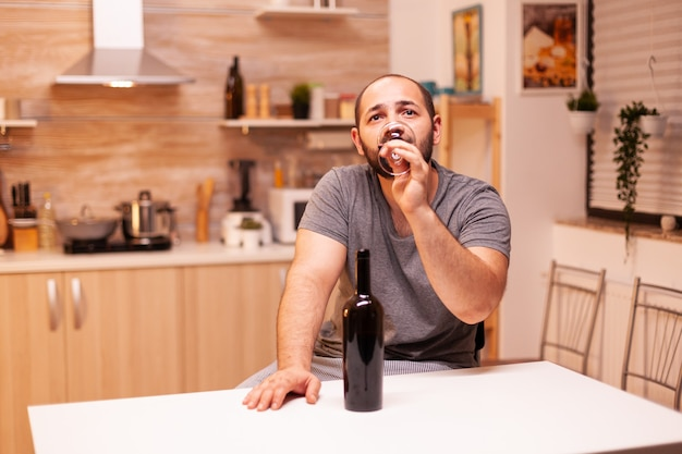 Man in solitude and frustration drinking a bottle of wine getting hangover. unhappy person disease and anxiety feeling exhausted with having alcoholism problems.
