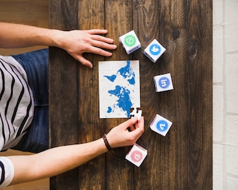 Man solving world map jigsaw puzzle near blocks of social networking icons