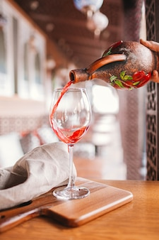 Man sommelier is holding glass of wine and tasting transparency light sediments in restaurant