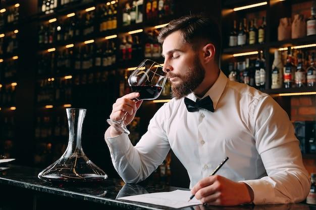 Мужчина-сомелье дегустирует красное вино в погребе