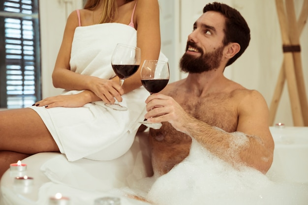 Man in spa tub with water and foam clanging glasses with woman