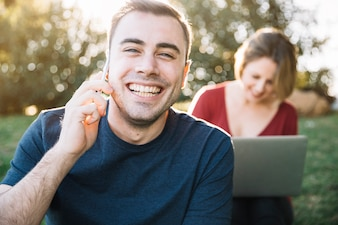 Man speaking on phone near woman with laptop