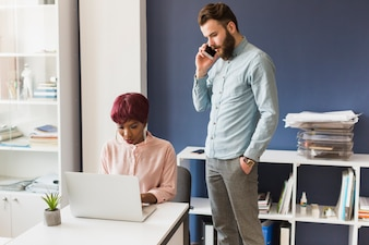 Man speaking on phone near working woman