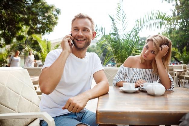 彼のガールフレンドが退屈している間電話で話す男。
