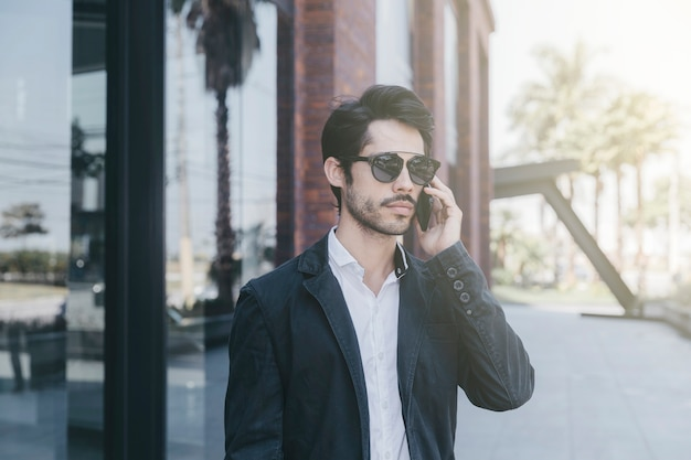 Man speaking on phone near glass wall