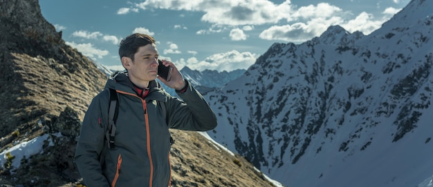 Man speaking on the phone on the top of a snowy mountain far from civilization. activity and communication availability