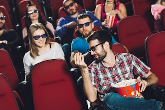 Мужчина разговаривает с друзьями в кино