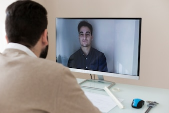 Man speaking with partner by video