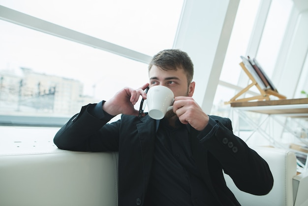 A man speaks by telephone and drinks coffee in a cafe near the window. a businessman dishes in a cafe