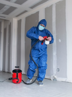 A man in a special suit paints walls with a spray gun, painting walls and ceilings