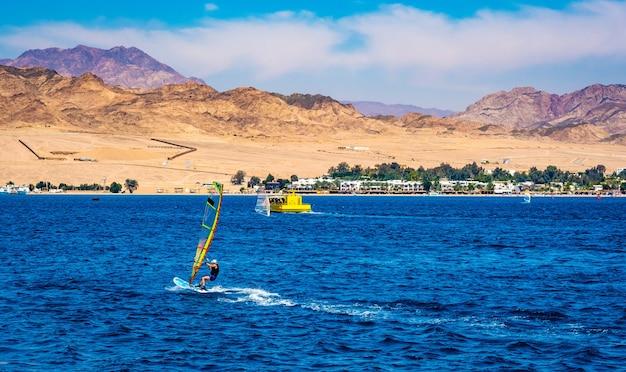 Человек проводит досуг с экстремальным виндсерфингом в синем море