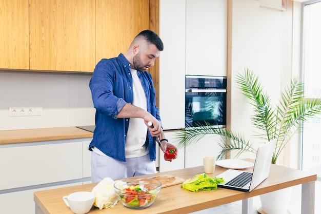 남자는 집에서 하루를 보낸다 부엌에서 야채의 아침 식사를 준비하는 남자 집에서 옷을 입고 수염을 가진 남자는 노트북을 사용하여 온라인 요리를 배웁니다
