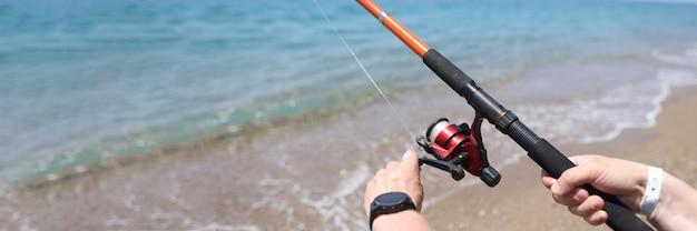 Человек вращает линию на катушке удочки в море. концепция правил любительской рыбалки