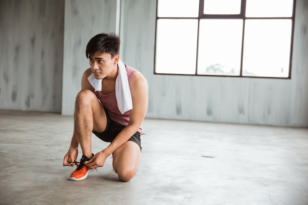 Man sport tie his shoes before workout