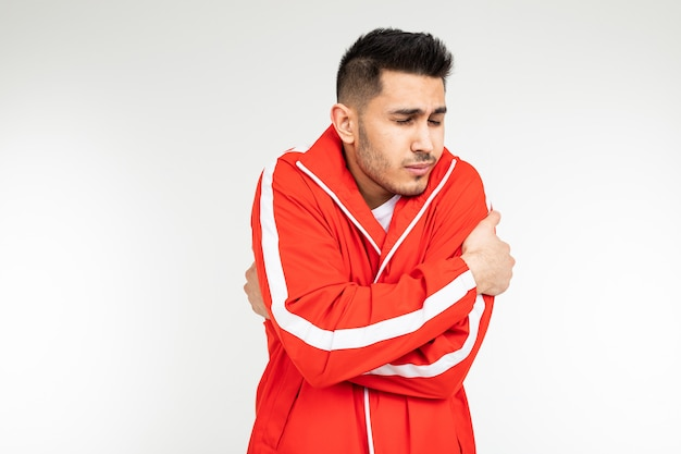 Man in a sports red suit shrinks from the cold hugging himself on a white background with copy space