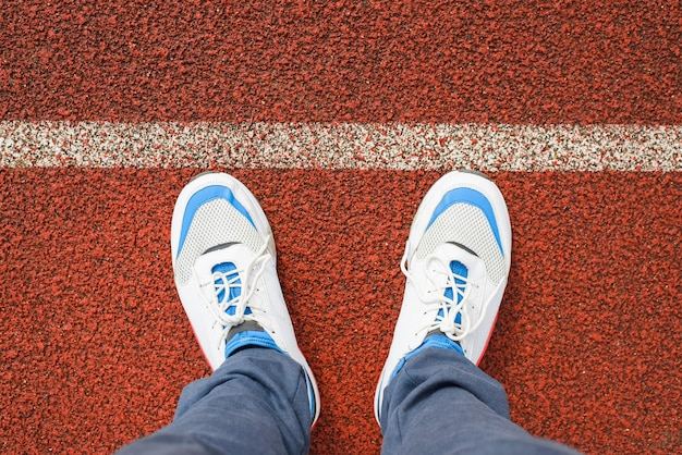 Man in sports white running shoes stands on the red jogging track in the stadium outside, close-up. top view, first person view