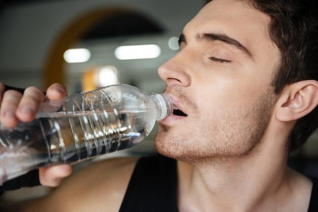 トレーニング後の男性スポーツマン飲料水