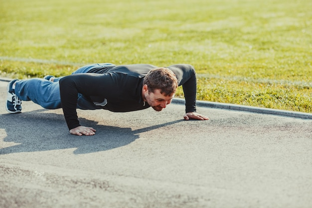 Man in sportswear performs push up outdoors. healthy and sport lifestyle
