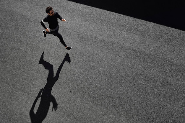Man in sportswear running on road