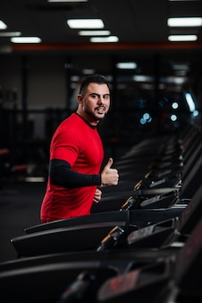 Man in sportswear running on treadmill at gym in red clothes
