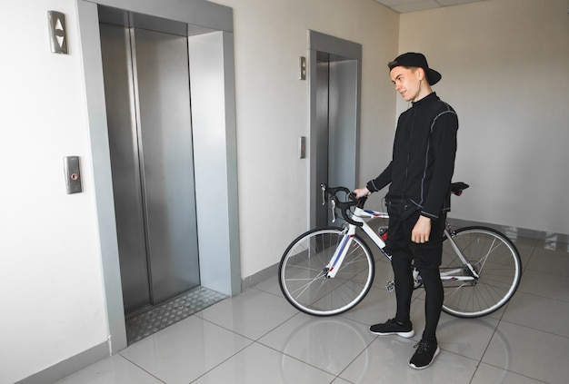 Man in sportswear stands in a bike home and waiting for an elevator