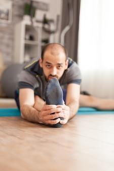 Uomo in abbigliamento sportivo che allunga le gambe sul tappetino da yoga durante la pandemia globale.