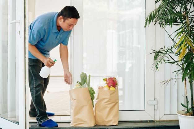 배달 된 식료품 패키지를 살포하는 남자