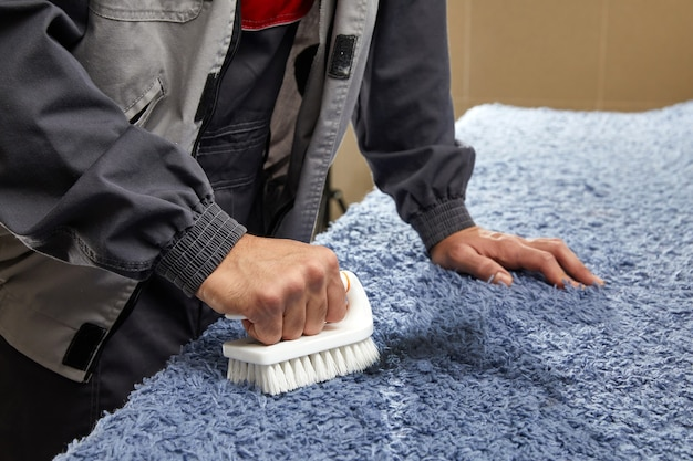 Человек распыляет моющее средство на сером ковре, чтобы удалить пятно в профессиональной уборке