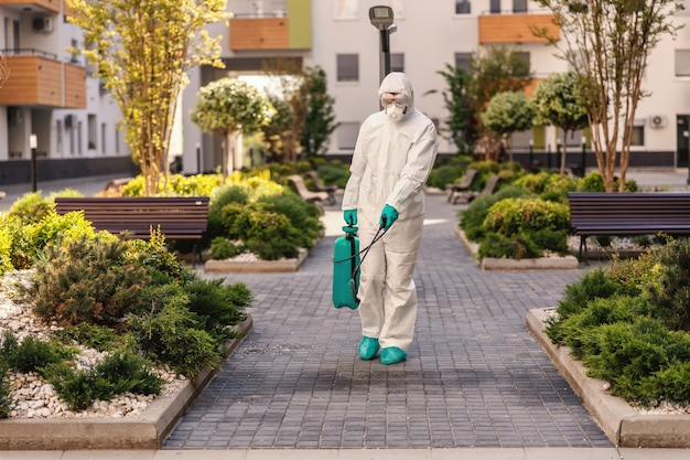 Man spraying outdoors in order to prevent coronavirus form spreading