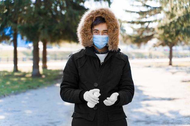 Мужчина распыляет антисептик на руки в белых медицинских перчатках
