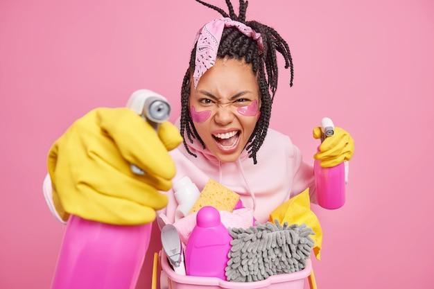 男は、洗浄用洗剤をスプレーし、にやにや笑い、顔の叫び声は、ピンクの壁に隔離された洗濯かごの近くに立ち、しわを減らすために目の下に美容パッチを否定的に適用します