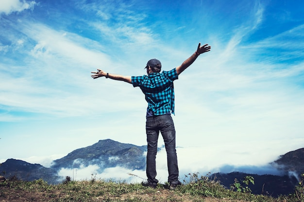 男は曇った青い空と高い山の頂上に向かって両腕を横に広げた。感情的なシーン。自由旅行の冒険とビジネスの勝利の概念。山の強風。ハンズアップ