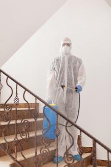Man spreading chemical against coronavirus wearing hazmat suit in office building.