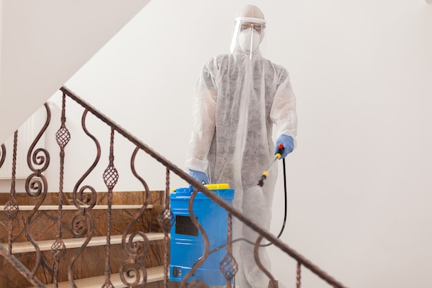 Man spreading disinfectant against covid-19 wearing biohazard costume.