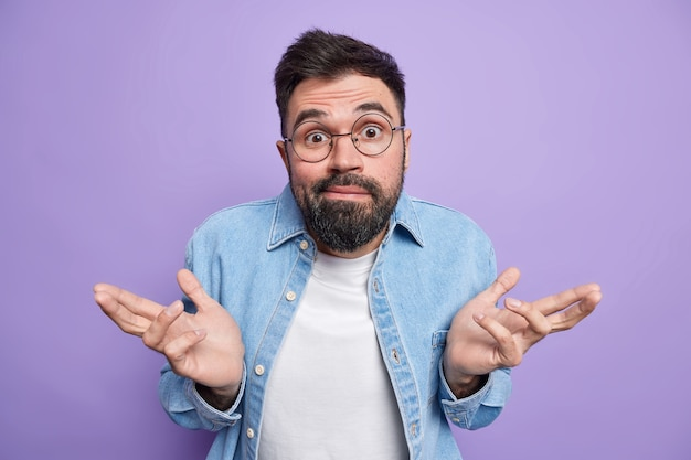 남자는 손바닥을 펼치고 무지하고 불확실하다고 느낀다. 선택을 할 수 없다. 둥근 안경을 쓴다. 데님 셔츠 포즈를 취한다.