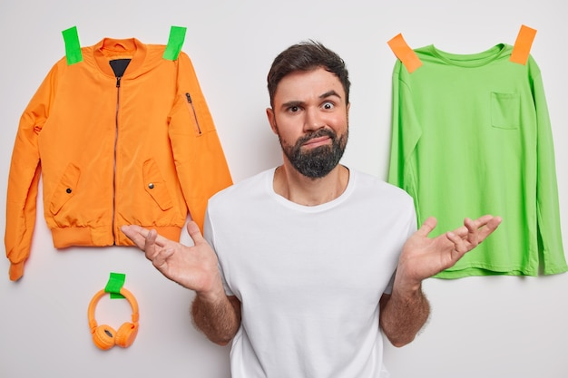 Man spreads palms feels hesitant about what to wear thinks about new purchase wears casual t shirt poses on white with plastered clothes and accessories