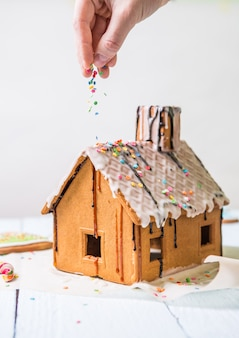 Man sprinkles homemade gingerbread house confectionery sprinkling