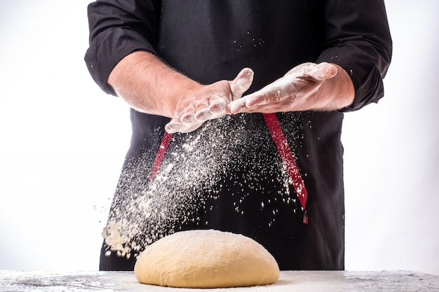 Man sprinkling flour over fresh dough on kitchen table. dough on white powder covered table
