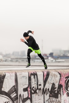 Man sprinting on rooftop on a rainy day