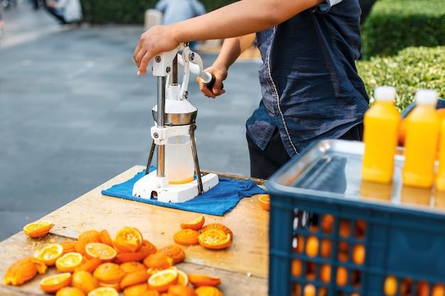 男は屋外でオレンジジュースを絞る