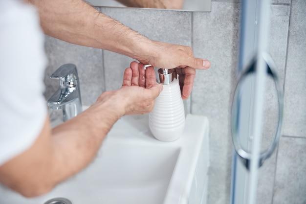 少量の液体石鹸を手のひらに詰める男性