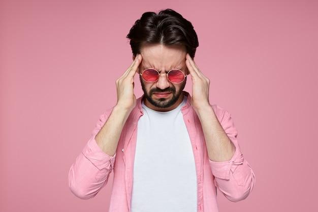 두통으로 고통받는 고통에 몸부림 치는 손으로 머리를 쥐고있는 남자