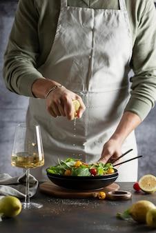 Человек выжимает лимон для здорового зеленого салата с красными и желтыми помидорами, изображение выборочного фокуса